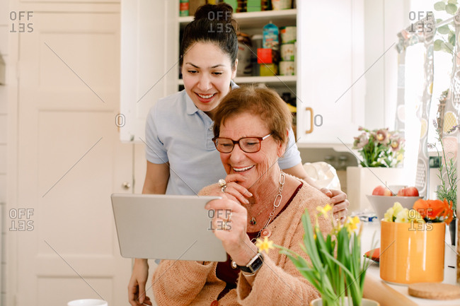 Smiling elderly woman and young female caregiver looking at digital tablet in nursing home kitchen