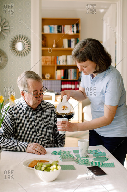 Mature female social volunteer pouring coffee for retired senior man in nursing home