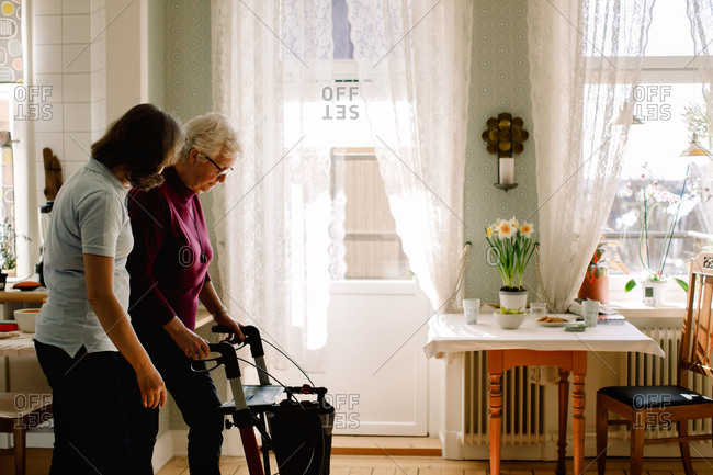 Side view of female healthcare worker assisting elderly woman with rollator in nursing home