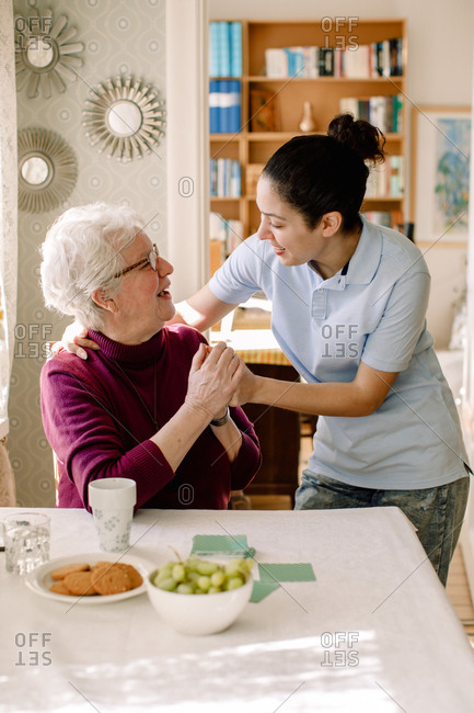Smiling retired senior woman holding hands of young female volunteer while talking in nursing home