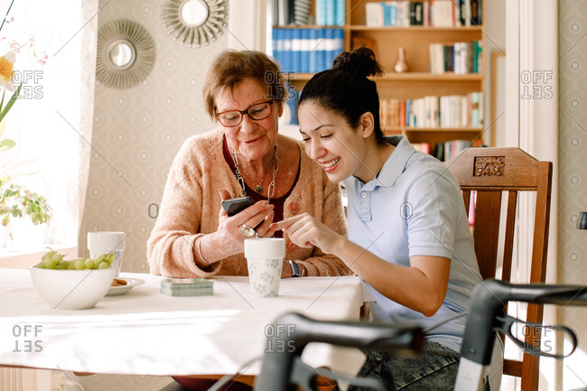 Smiling young female social service worker assisting retired elderly woman using smart phone at table in nursing home