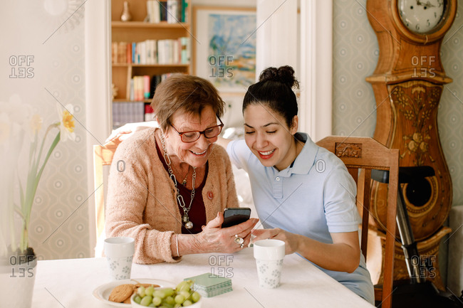 Smiling young female volunteer assisting retired elderly woman using smart phone at table in nursing home