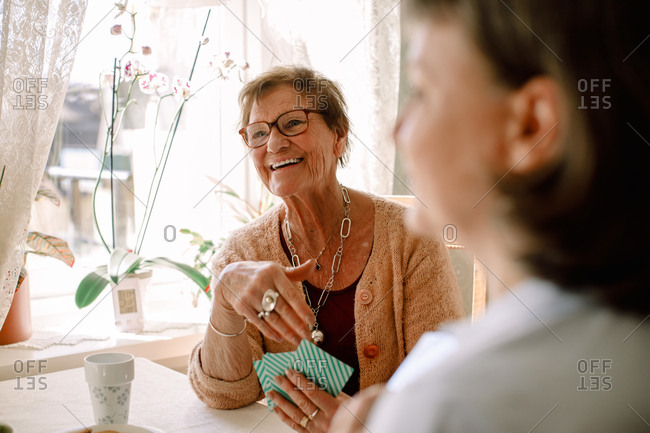 Smiling retired senior woman looking away while playing cards with social worker at nursing home