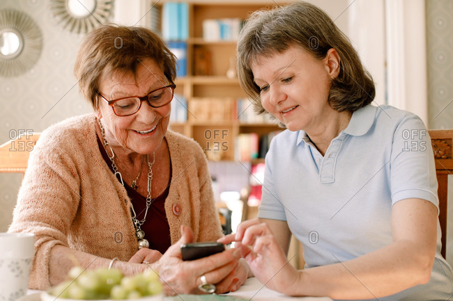 Smiling healthcare worker is assisting elderly woman in using smart phone at nursing home.