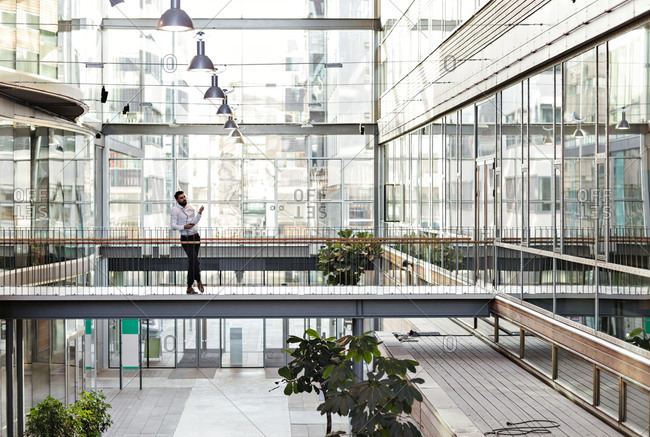 Full length of young businessman standing at atrium in office