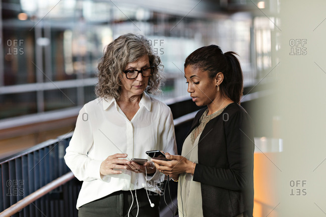 Female business colleagues talking while using smart phones at office lobby