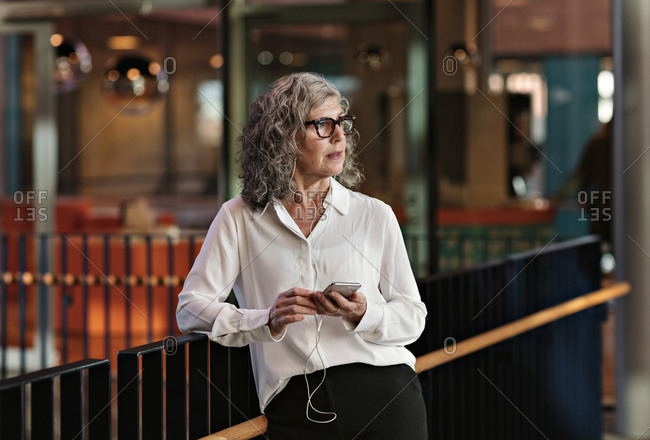Contemplating senior businesswoman using smart phone while standing at railing in office