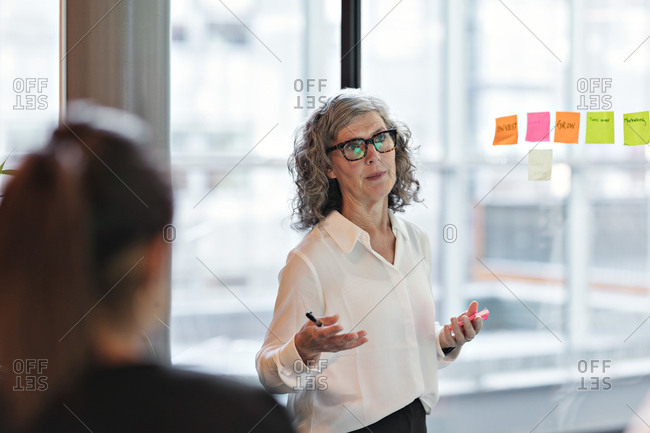 Senior confident businesswoman giving presentation in board room at office