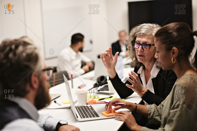 Confident mature professional discussing with colleagues in meeting at conference table