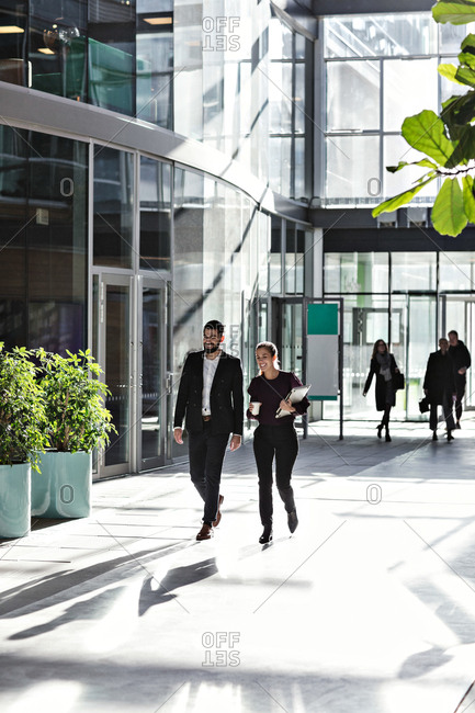Full length of smiling business coworkers talking while walking in atrium