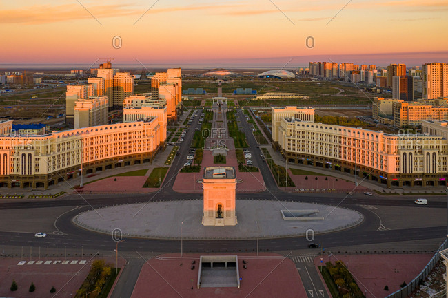 September 30, 2018: Aerial view of the Arch of Triumph, Nur Sultan, Kazakhstan. Taken at sunrise with the light casting a golden orange on the rooftops of the buildings.