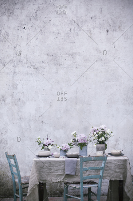 Table setting for an outdoor spring lunch with white linen tablecloth, ceramic bowls and flowers