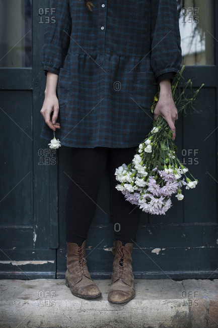Close-up of a woman wearing leather boots who's holding a bunch of flowers