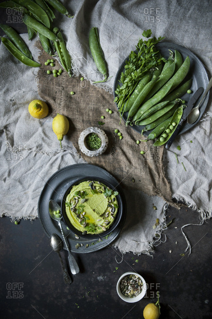 Overhead view of a bowl of pea humus on a rustic table with ingredients