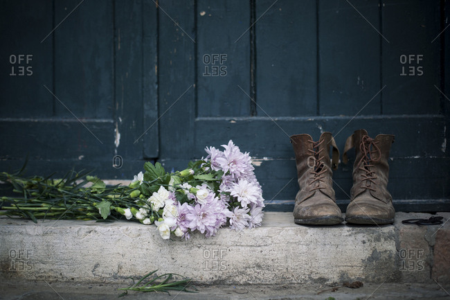Bunch of buttercup flowers laid on the threshold of a door together with an old pair of leather boots