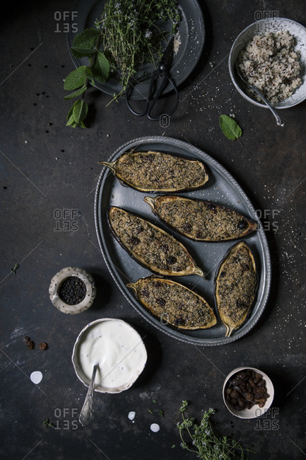 Overhead shot of a tray of vegan stuffed eggplants on a rusty table with ingredients