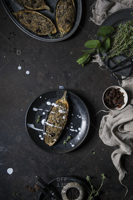 Vegan stuffed eggplant served on a black plate with yogurt sauce on a rusty table with ingredients