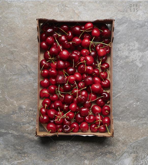 Overhead view of box of ripe cherries