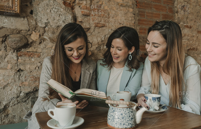 Three happy young women reading a book in a cafe