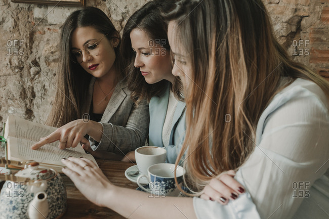 Three young women reading a book in a cafe