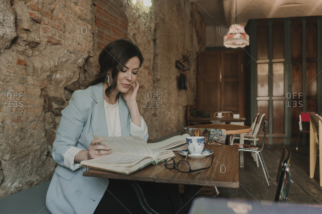 Young woman reading a book in a cafe