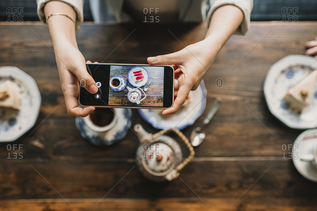 Top view of woman taking a photo of cake and tea in coffee shop
