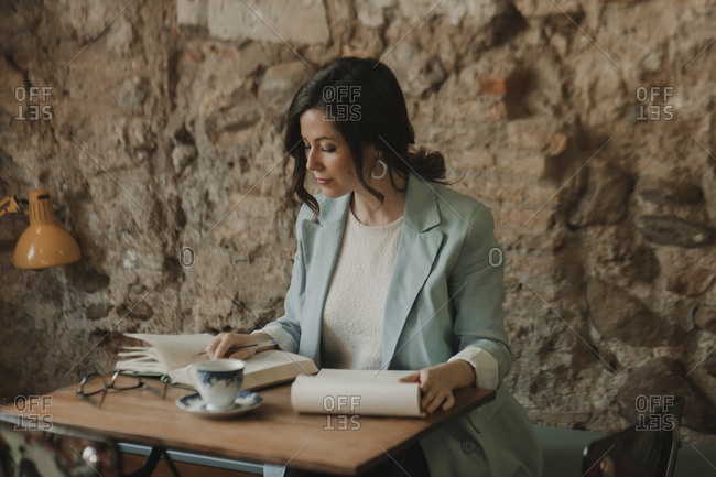 Young woman taking notes and reading a book in a cafe