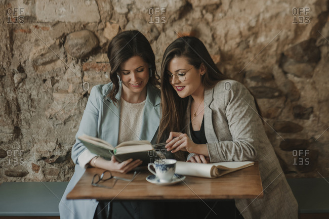 Two young women with notebook and book in a cafe