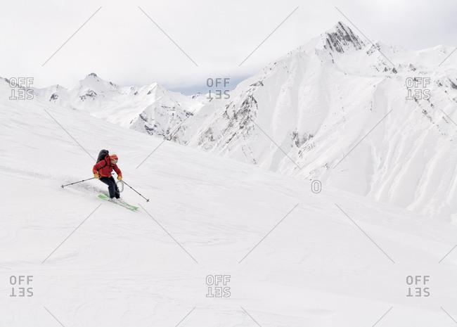 Georgia- Caucasus- Gudauri- man on a ski tour riding downhill