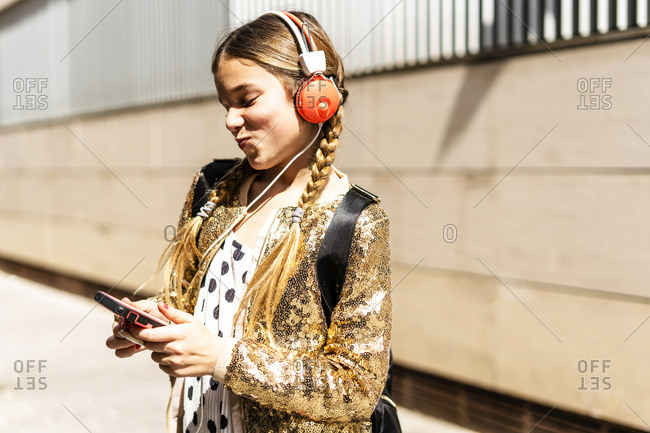 Smiling girl wearing golden sequin jacket and headphones looking at cell phone