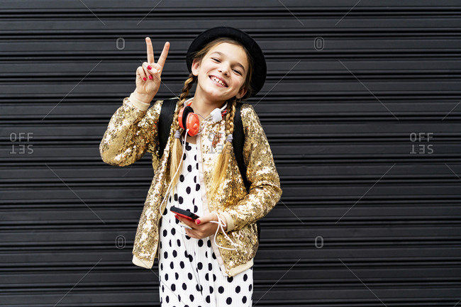 Portrait of happy girl with smartphone wearing hat and golden sequin jacket showing victory sign