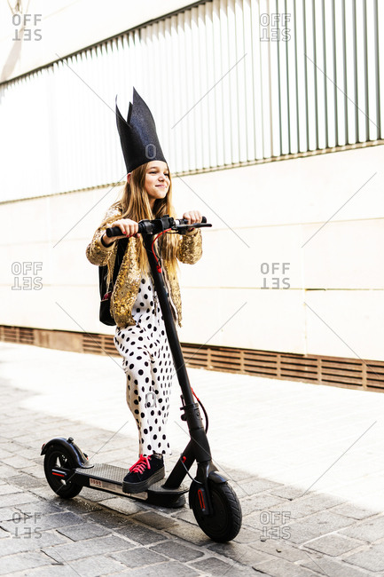 Portrait of smiling girl with E-scooter wearing black crown- golden sequin jacket and polka dot jumpsuit