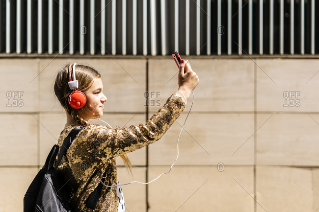 Girl with backpack and headphones taking selfie with smartphone