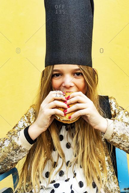 Portrait of girl wearing black crown eating Hamburger