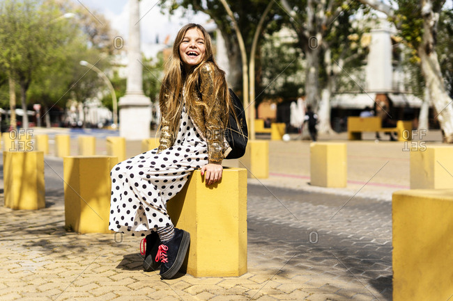 Portrait of stylish girl sitting on bollard laughing