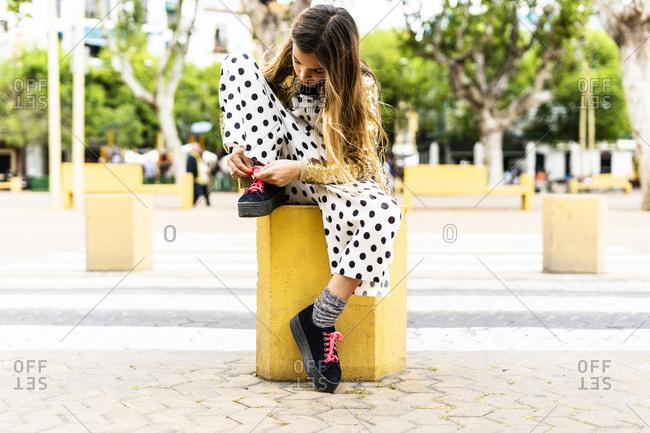 Girl sitting on bollard tying shoe