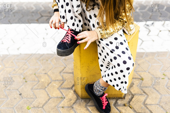 Girl sitting on bollard tying shoe- partial view