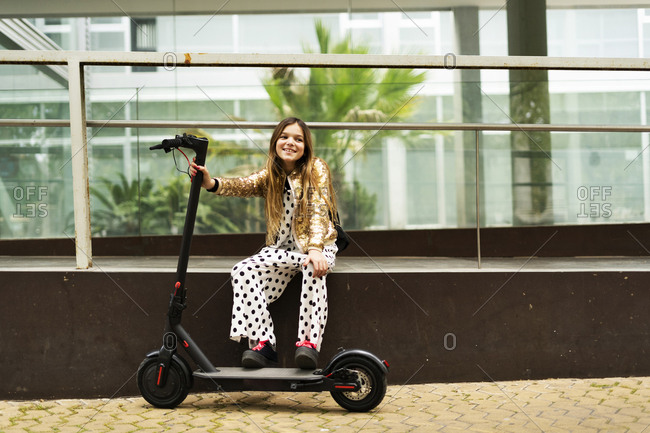 Portrait of smiling girl with E-Scooter wearing golden sequin jacket and polka dot jumpsuit