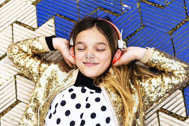 Portrait of happy girl wearing golden sequin jacket listening music with headphones