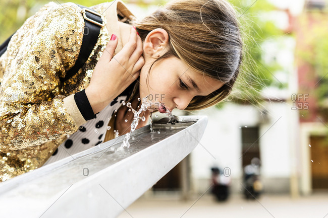 Girl drinking water of a fountain