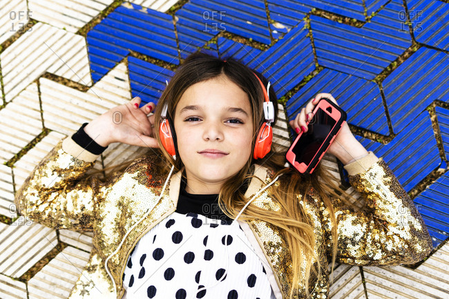 Portrait of girl wearing golden sequin jacket listening music with headphones and smartphone