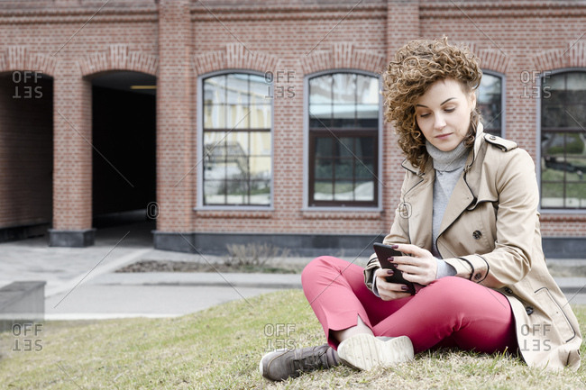 Portrait of woman with curly hair sitting on a meadow looking at cell phone