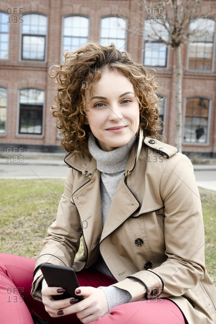Portrait of smiling woman with smartphone wearing trenchcoat sitting on a meadow