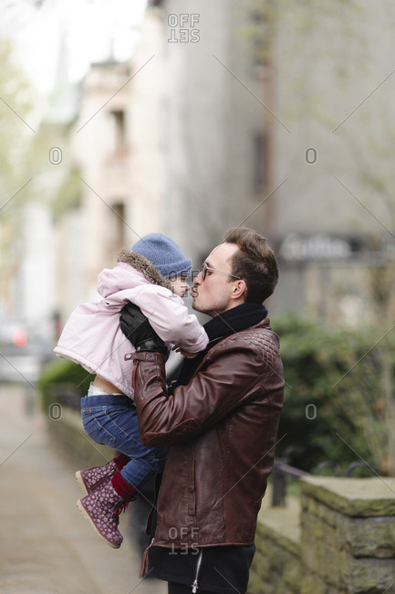 Father holding and kissing his daughter in the city