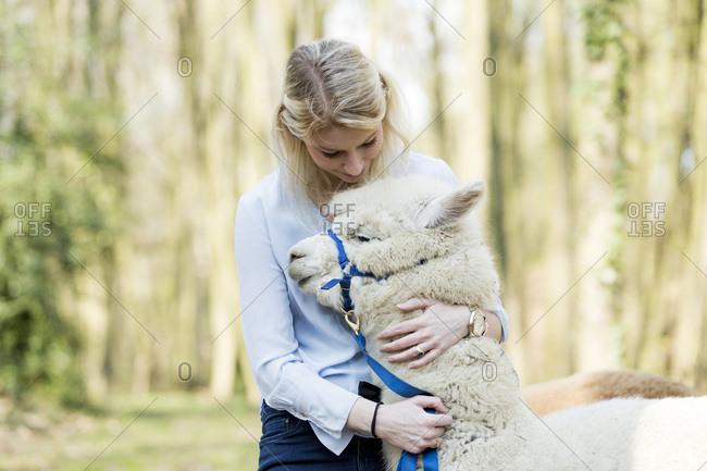 Woman cuddling alpaca