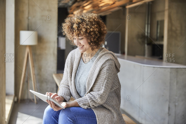 Smiling woman using tablet in modern office