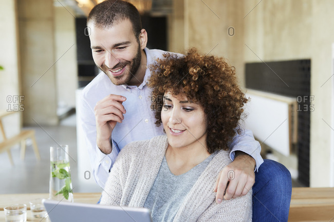 Happy man and woman sharing tablet in modern office