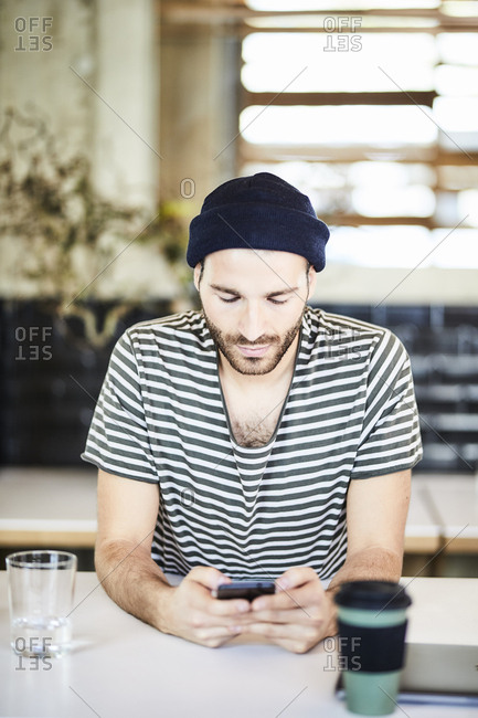 Young man wearing a beanie using cell phone