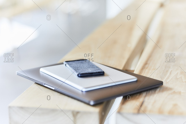 Stack of mobile devices on wooden bench