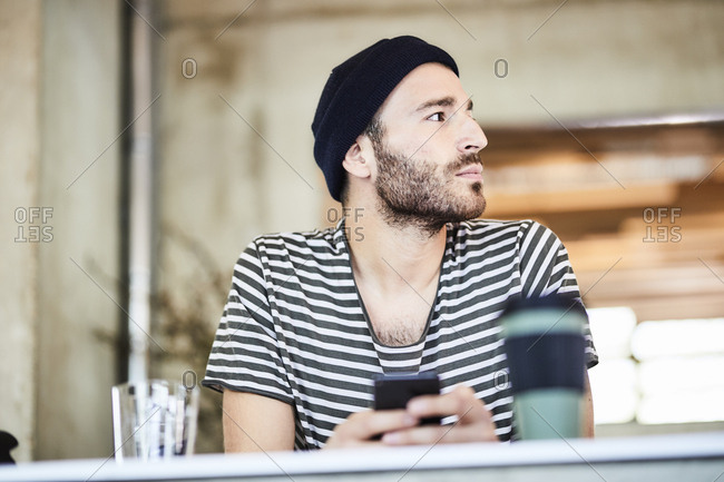Young man with cell phone wearing a beanie looking around